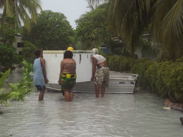 Tuvalu - locals moving a fridge following flooding