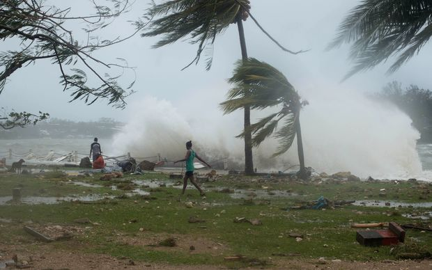 Waves and scattered debris along the coast, caused by Cyclone Pam