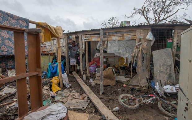 Residents in the remains of their cyclone-damaged home.