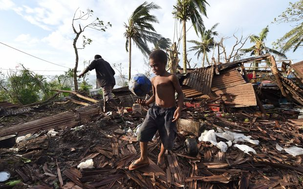 A young boy kicking a ball as his father searches through the ruins of their family home in Vanuatu's capital Port Villa after Cyclone Pam ripped through the island nation.
