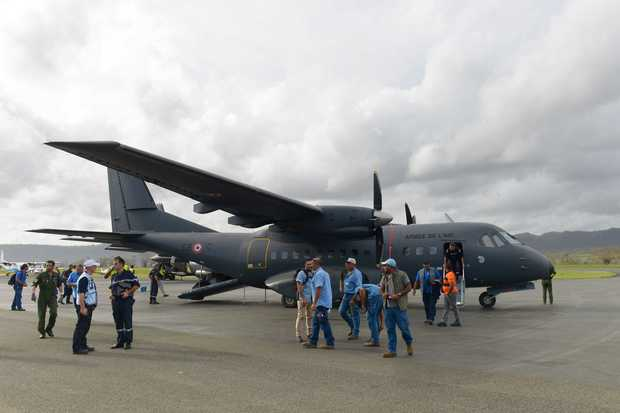 Rescuers standing by a French Army Casa logistics and transport plane, carrying relief and assistance after cyclone Pam.
