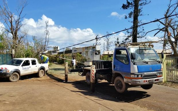 Workers from Vanuatu's electricity provider UNELCO repair power lines