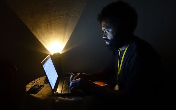 Radio New Zealand International reporter Koroi Hawkins works without power.