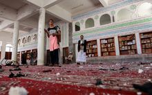 Armed men inspect the damage following a bomb explosion at the Badr mosque in southern Sanaa, Yemen.