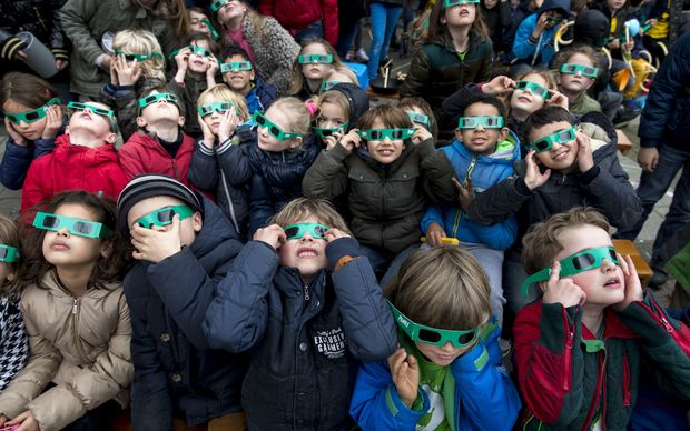 School children wear protective eye gear to watch a partial solar eclipse from their school yard in Amsterdam.
