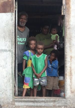 Grandfather Sakaio Cook stands in the doorway of his house, one of only two on Mataso that survived cyclone Pam, with daughter Leimas carrying baby Margaret, Rexson in the green shirt, Ellen in the blue shirt and Leika in the vanuatu dress(green yellow and red).