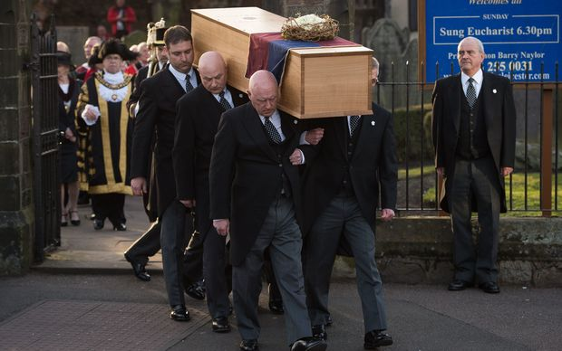 The oak coffin with the remains of King Richard III is carried out of St Nicholas Church in Leicester.