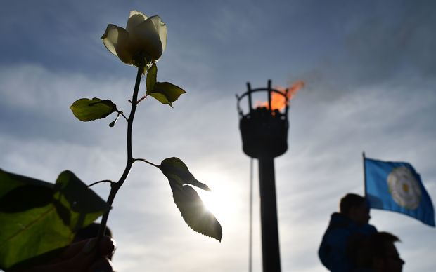 A member of the public holds a white rose in front of the battlefield beacon following a ceremony for King Richard III