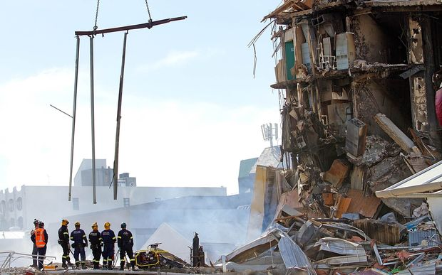Rescuers stand at the smoking ruins of the CTV building.