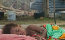 A child sleeps outside the New Covenant Church in Sangava Village