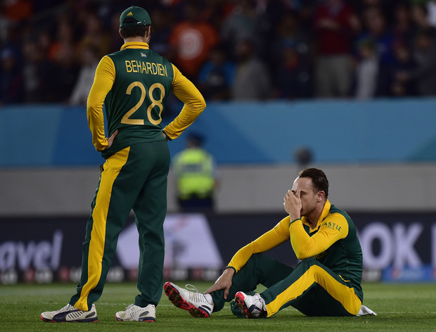 South Africa's Faf du Plessis (R) sits dejected on the field with teammate Farhaan Behardien after their loss.