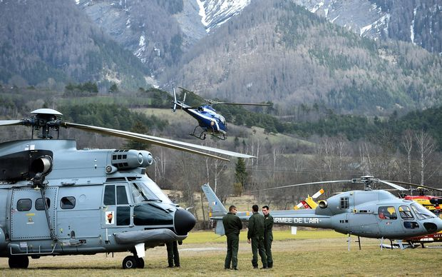 Rescue helicopters near the site of the crash in a remote mountain area.