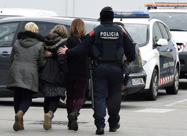 Police escort family members of an aircrash victim at Barcelona's airport.