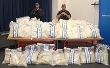 Sydney police officers stand near packages containing illicit drugs during a media conference last year.