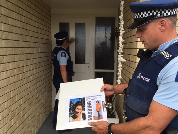 Police teams are going door-to-door in the Cable Bay and Taipa areas. Constable Kate Korach (knocking on the door) and Constable Marco Van Den Broek (holding the photo).