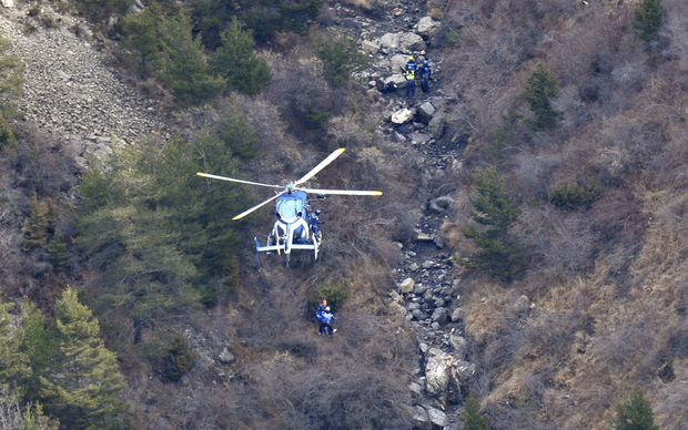 A helicopter lowers search and rescue personnel close to the crash site of the Germanwings Airbus A320 in the French Alps.