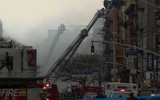 New York firefighters battle a blaze at a commercial and residential block.