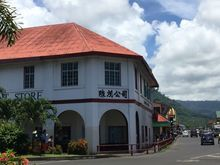White 2 story Chinese supermarket in Apia, Samoa with terracotta tiled roof and Chinese signage. .