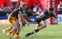 Warriors player Shaun Johnson is grabbed by the Broncos