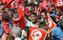 Tunisians wave their national flag and chant slogans during a march against extremism outside Tunis' Bardo Museum.