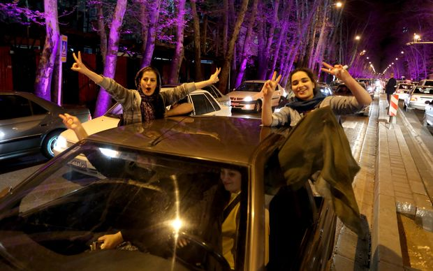 "Women sitting in a car flash the ""V for Victory"" sign as they celebrate on Valiasr street in northern Tehran."