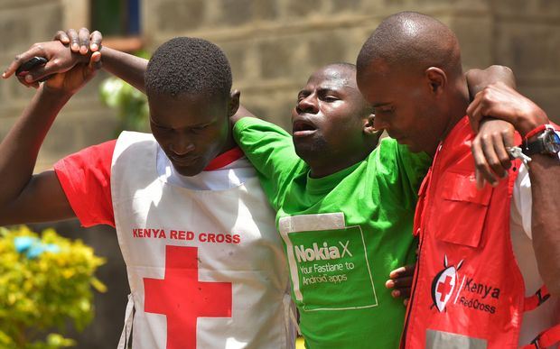 Red Cross workers help a relative of one of the students killed by al-Shabaab gunmen.