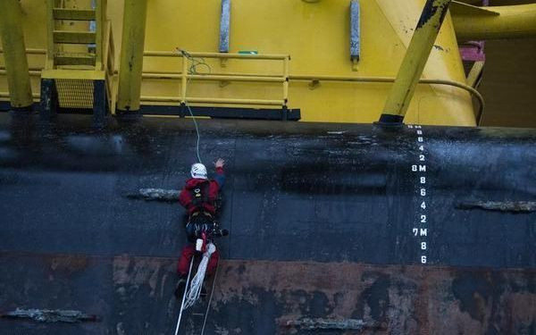 A Greenpeace activist scales the Polar Pioneer drill rig in the Pacific Ocean.