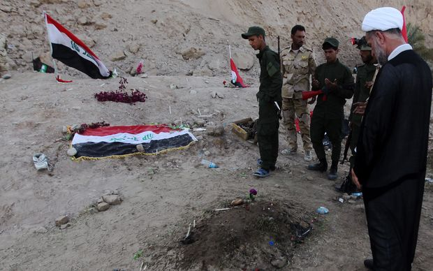 Iraqi Shiite fighters and members of Iraq's Popular Mobilisation, pray at a burial site believed to hold victims of a June massacre.