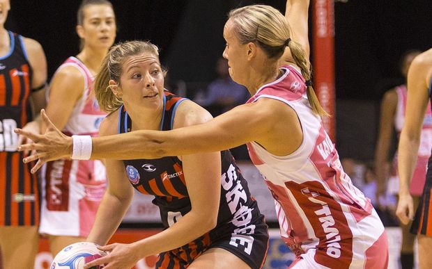 The Tactix Anna Thompson passing the ball for under pressure from Adelaide defender Renae Hallinan.