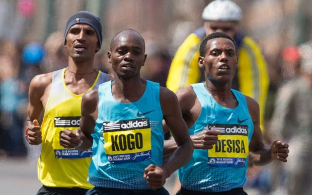 Gebregziabher Gebremariam (left), Micah Kogo (center), and Lelisa Desisa (right), pass the 24 mile marker on Beacon Street during the Boston Marathon.