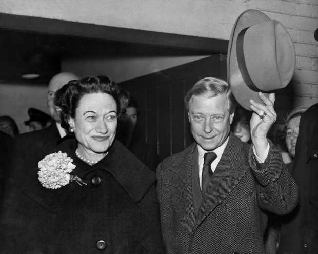 Edward, Duke of Windsor (R), with his wife the Duchess Wallis of Windsor, waves his hat to the welcoming crowd as they arrive at Victoria Station in London, from Paris, 13 November 1956. This is their first visit together to Britain since 1953.