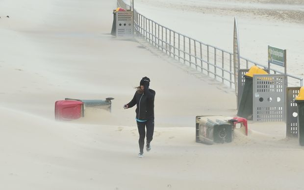 A jogger struggles against sand whipped up by strong winds at Bondi Beach in Sydney.