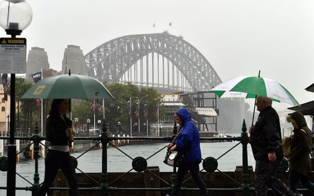 Commuters make their way in the heavy rain in front of the Sydney Habour Bridge.