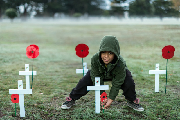 A child places a poppy at the dawn service at Tolaga Bay, near Gisborne.