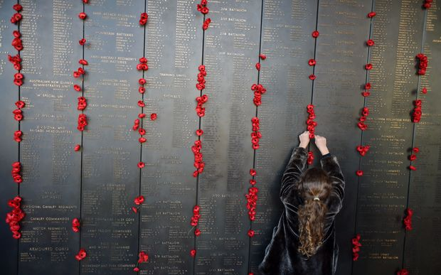 A girl places a poppy at the Roll of Honour at the Australian War Memorial after the ANZAC Day dawn service in Canberra, Saturday, April 25, 2015.