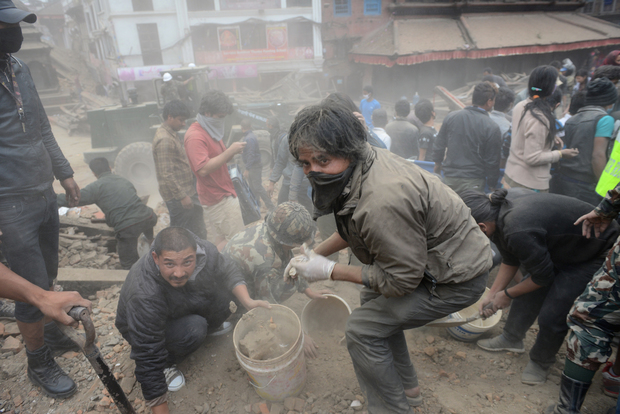 People work to clear rubble in Durbar Square, surrounded by dust.