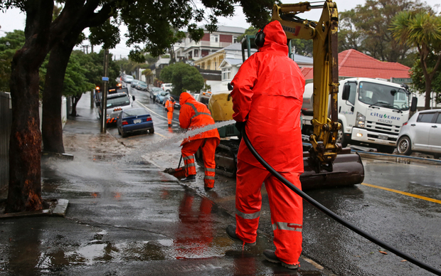 Contractors cleaning up remnants of mud and silt that flooded Wright Street, Mount Cook, Wellington.