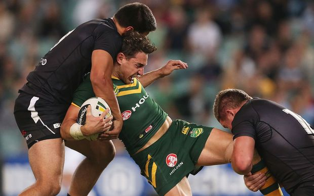 The Kangaroos fullback Billy Slater is tackled by two Kiwis players.