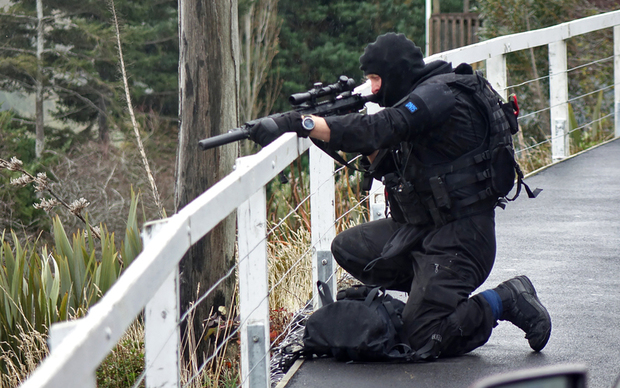 AOS member in sniper position giving cover.