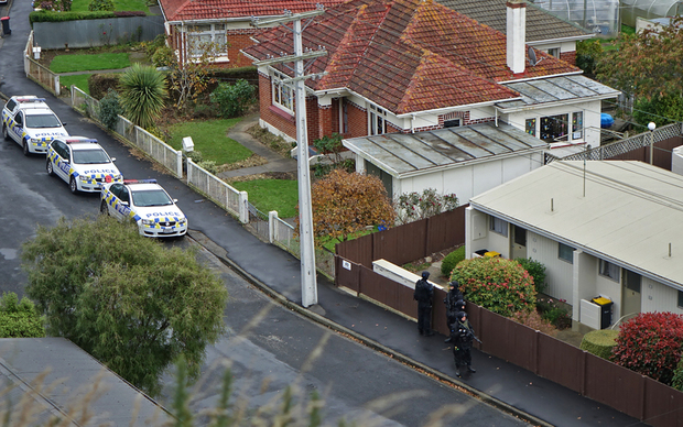 Armed offenders squad members search a Dunedin street.