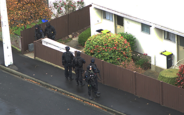 Armed offenders squad members outside a Dunedin house.