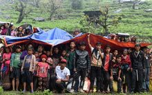 Nepalese villagers shelter from rain under foam and plastic sheets at they wait for aid