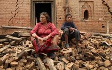 Nepalese woman and child on rubble in the village of Sathighar, north of Katmandu, 29 April.
