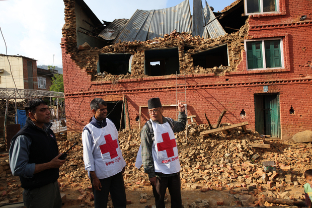 Members of the Nepal Red Cross look at a damaged building in Kathmandu.