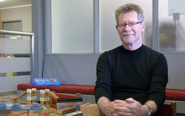 The Ministry of Health's Advisor on Child and Youth Health,  Pat Touhy, sits next to toy train set in outpatients