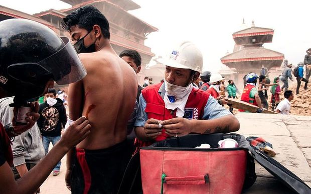 Red Cross workers assist a man in Nepal.