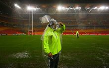 Security guards survey Brisbane's sodden Suncorp Stadium ground.