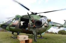 An Indian Air Force (IAF) helicopter pilot unloads relief aid in the village of Laprak.