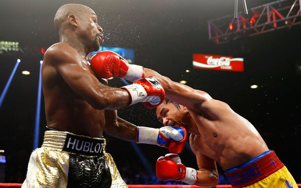 Floyd Mayweather exchanges punches with Manny Pacquiao.