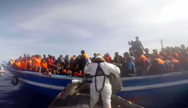 This image grab made from a handout video released by the Italian Coast Guard (Guardia Costiera) on May 3, 2015, shows an Italian coast guard taking part in a rescue operation of a boat carrying 397 migrants, on May 2, 2015, in the Mediterranean Sea.